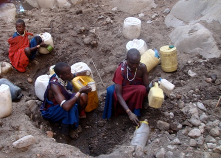 Maasai ladies collecting dirty water from a dry riverbed one cup at a time.